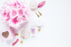Pink feminine styled stock photo. Pink flat lay on white background with flowers, candles and jewelry stock photo