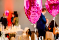 Pink festive balloons shape of heart with the party guests in the background.  Royalty Free Stock Photography