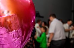 Pink festive balloons shape of heart with the party guests in the background Royalty Free Stock Photo