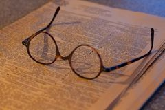Pink financial paper with antique spectacles royalty free stock photos