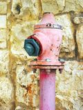 Pink Fire Hydrant. An old and rusting faded pink fire hydrant, once bright red but now faded from sun and water exposure. Installed beside a yellow Jerusalem Royalty Free Stock Images