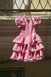 Pink flamenco dress for little girl hangs in Centro old district of Sevilla Spain Stock Photo