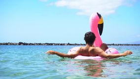 Pink flamingo on beach. Someone swimming on pink inflatable flamingo on summer sea stock footage