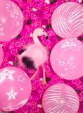 Pink flamingo, soft toy and balloons on a pink background with hearts. The concept of holiday gifts and decorations stock photo