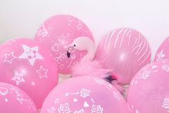 Pink flamingo, soft toy and balloons. The concept of holiday gifts and decorations. Background royalty free stock image