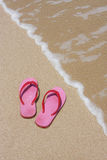 Pink flip flops. Colorful pink flip flops on beach next to the water royalty free stock photos
