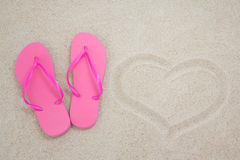Pink flip flops and heart on sandy beach Stock Image