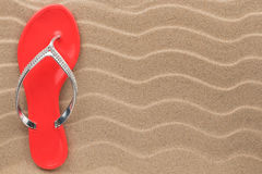 Pink flip flops with rhinestones on the wavy sand. Stock Images