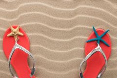 Pink flip flops and starfish on the sand of the beach. Concept of rest. View from above royalty free stock images