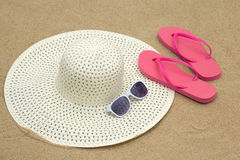 Pink flip flops, sunglasses and hat on beach sand Royalty Free Stock Image