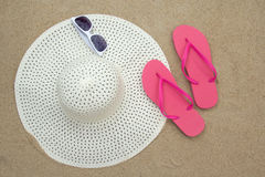 Pink flip flops, sunglasses and hat on sandy beach Royalty Free Stock Photography