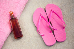Pink flip flops and suntan lotion bottle on sandy beach Royalty Free Stock Images
