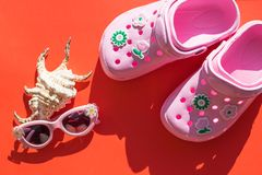 Kids Footwear .Modern Rubber sandals.Pink flip flops with seashell and sunglasses on red background.Summer rubber flip royalty free stock photos
