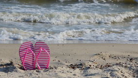 Pink flip flops on yellow sandy beach near sea. Waves, nobody. Summer vacation concept stock footage