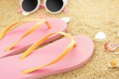 Pink flipflops on beach sands. Close up portrait of pink flipflops on beach sands Stock Photo