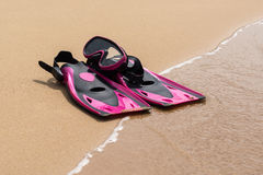 Pink flippers on the sand of beach with wave on background.  Royalty Free Stock Photo