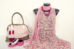 Pink floral dress on mannequin with matching accessories. Summer dress on tailor's dummy with purse, scarf and jewellery Royalty Free Stock Photos