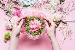 Pink Florist workspace with Lilies and other flowers, glass vase with water. Female hands making  Festive Flowers arrangements Royalty Free Stock Photo