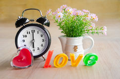 Pink flower and alarm clock. Royalty Free Stock Images