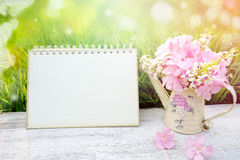 Pink flower,blank page paper of calendar over nature green grass in soft pastel tone Royalty Free Stock Photography