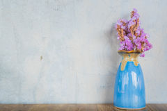 Pink flower in blue vase on a wooden table Stock Photo