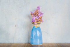 Pink flower in blue vase on a wooden table Stock Photography