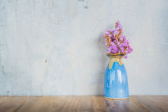 Pink flower in blue vase on a wooden table Stock Images