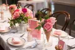 Pink flower design on the served restaurant table for Sunday girly brunch party. royalty free stock photos