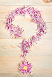 Pink flower petal arrange on wooden background as a question mar Stock Photos