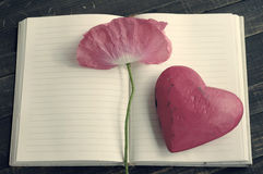 Pink flower of poppy on an open notebook and one decorative hearts. Stock Photography