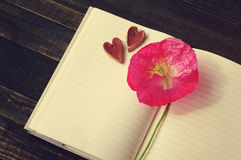 Pink flower of poppy on an open notebook and two decorative hearts. Stock Photography