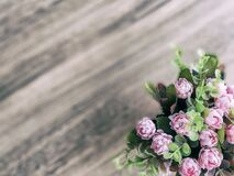 Pink flower pot on the corner of the wooden table and leave blank space