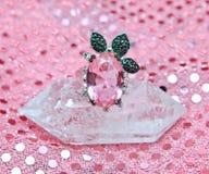 Pink Flower Ring. Pink Kunzite flower ring on quartz crystal with femine metallic pattern background Stock Photography