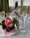 Pink flower and wine glasses. Pink primula in gift wrapping with glasses and bottle on table Royalty Free Stock Photography