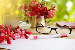 Pink flower on wooden table with including notebook paper page business or education background Royalty Free Stock Image