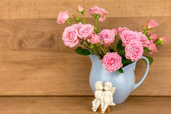 Pink flowers in blue jug. Stock Images
