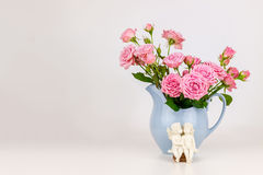 Pink flowers in blue jug. Stock Photography