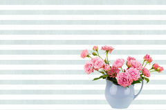 Pink flowers in blue jug on watercolor blue stripes background. Stock Images