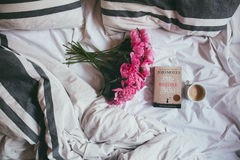 Pink Flowers Beside Brown Book Beside White Ceramic Mug With Brown Coffee on Top of White Textile Stock Photo