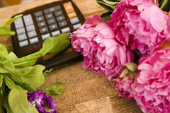 Pink flowers beside calculator on table in flower shop, close-up (still life) Stock Images