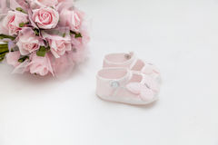 Pink flowers and children's sandals on the white bed Stock Photos