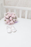 Pink flowers and children's sandals on the white bed Royalty Free Stock Photography