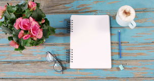 Pink flowers, cup of coffee, diary, binder clip and spectacles. On wooden surface stock video