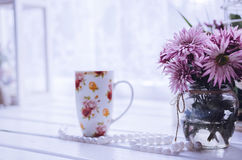Pink flowers with cup of coffee or tea near the window Stock Photo