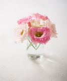 Pink flowers (eustoma) on old rustic  table. Stock Photos