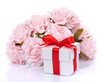 Pink flowers and  gift box with red ribbon and bow on a white ba Royalty Free Stock Images