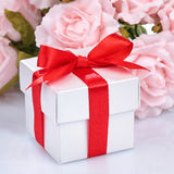 Pink flowers and  gift box with red ribbon and bow on a white ba Royalty Free Stock Photo