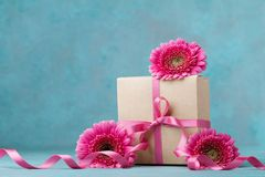 Pink flowers and gift box with ribbon on turquoise table. Greeting card for Birthday, Woman or Mothers Day. Stock Images