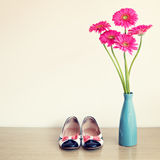 Pink flowers and girly shoes. Pink flowers in a blue vase with girly shoes Royalty Free Stock Image