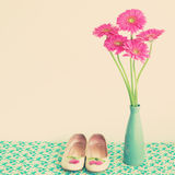 Pink flowers and girly shoes. Pink flowers in a blue vase with girly shoes Stock Photo